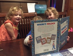 Three kids looking for Waldo in Where's Waldo book