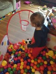 Toddler in pop up ball pit filled with balls with basketball hoop