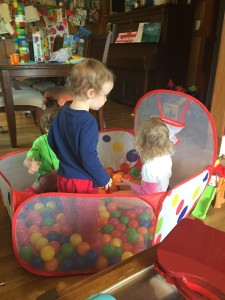 Three kids ages 2 4 and 6 inside pop up ball pit filled with balls
