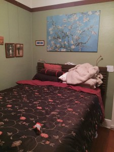 Bedroom with bed made and art hanging on wall over headboard