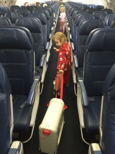 Preschooler child puling Jet Kids Bed Box down aisle of empty airplane