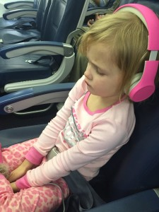 Child dressed in pink wearing pink kids headphones onboard airplane