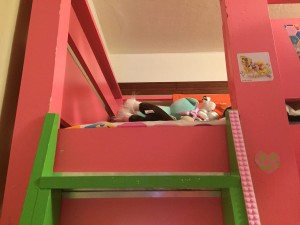 Mayka toy block tape attached along green ladder to pink bunk bed
