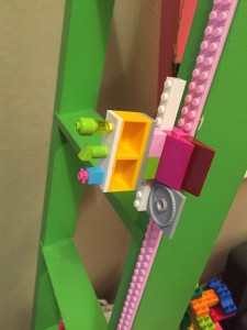 Lego creation attached to pink Mayka toy block tape stuck to green ladder