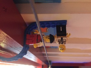 Lego minifigs stuck sideways and hanging upside down from Mayka toy brick block tape in blue underneath bunk bed