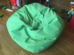Green bean bag chair in middle of floor with toys