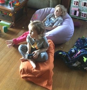 Kid sitting on purple floral bean bag chair with another kid sitting on orange pillow in front
