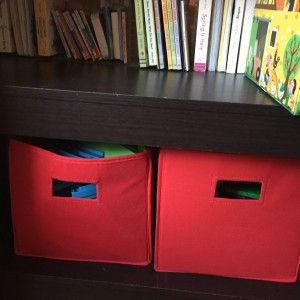 Storage bins in red on bottom shelf of bookshelf holding toys