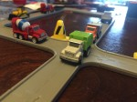 Driven pocket series green tiny dump truck on gray connecting road pieces