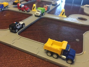 Driven pocket series dump truck blue yellow on interconnecting gray road pieces set up