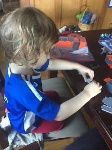 Preschooler playing with tiny trucks and road pieces on table