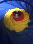 Inside a pop up tunnel for kids in blue yellow and red