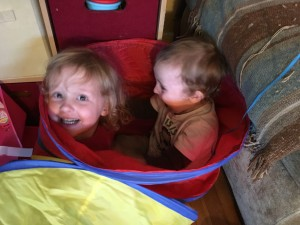Two kids inside the pop up tunnel at the same side