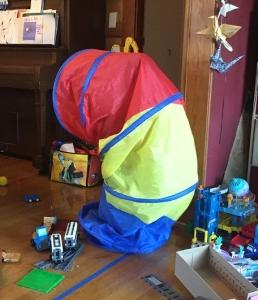 Child standing hidden inside kids pop up tunnel