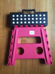 Step stool acko folded flat for storage with red base and black top with white dots