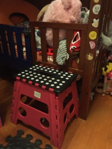 Acko step stool red and black set up next to toddler bed