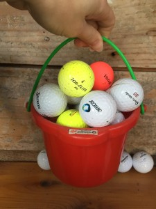 Spielstabil small german company bucket sand pail filled with golf balls and held aloft