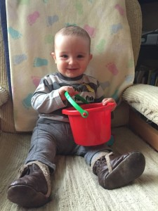 toddler sitting in rocking chair with red spielstabil bucket