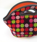 BYO by Built neoprene lunch bag in green orange pink and red polka dot pattern on brown background lined with orange interior
