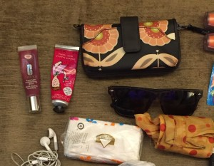 lip gloss, hand cream, wallet, sunglases, tissues laid out together