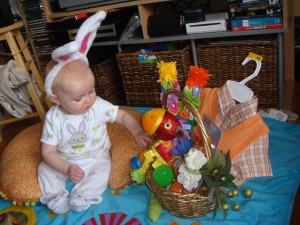 Infant wearing bunny ears exploring contents of easter basket
