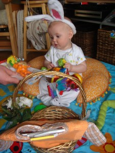 Baby clothes in Easter basket with infant in bunny ears sitting behind it