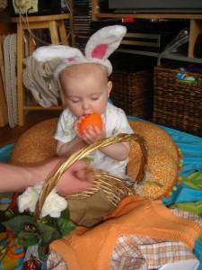 Baby chewing on jumbo plastic easter egg