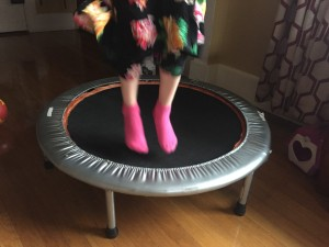 Child's feet in pink socks while jumping on exercise trampoline