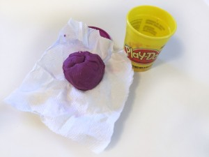 Play-Doh ball on top of dry paper towel next to container