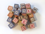 Uncle Goose wooden classic ABC blocks in Polish in pile on white surface