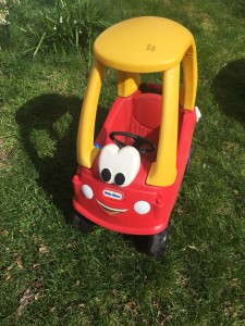 Cozy Coupe red car with yellow roof and steering wheel parked on grass