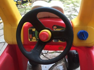 Interior of little tikes cozy coupe red car with black wheels and yellow roof