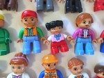 Duplo people lined up in rows with different sizes genders and skin tones