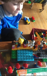 Seven year old playing with Duplo people figurines