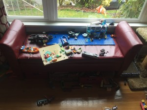 Homepop Target red faux leather settee storage bench in front of window covered in lego