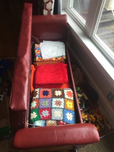 Homepop red faux leather storage bench shown open with blankets inside and bins of toys stored underneath
