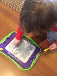 Child drawing and stamping on magna doodle magnetic drawing board