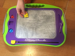 Child's hand with gray magna doodle board