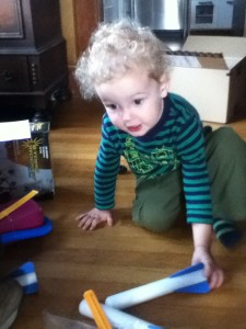 Toddler playing with foam rockets from stomp launcher