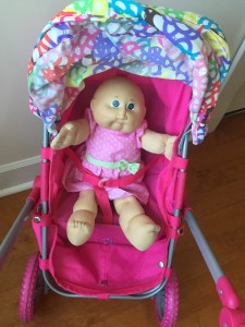 Doll strapped into upright sitting position on Lissi city stroller