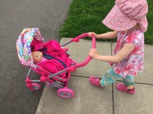 Child pushing Lissi stroller on sidewalk
