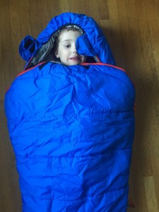 Child inside REI Nodder kids sleeping bag in blue with red zipper accents