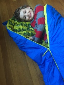 Seven year old laying in REI kids kindercone sleeping bag in blue