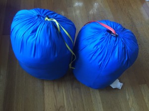 Kindercone and Nodder REI kids sleeping bags in blue side by side in stuff sacks