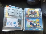 Lego instruction manuals stored in page protectors inside three ring binder