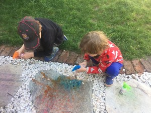 Kids spraying sidewalk chalk on walkway