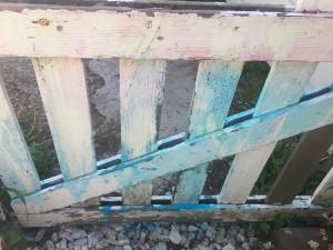Sidewalk chalk spray on white picket fence when dry