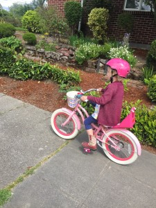 Child riding pink and white bike wearing hot pink wipeout helmet decorated with dry erase markers