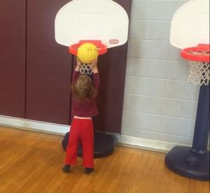 Toddler putting dodgeball in Little Tikes adjustable basketball hoop