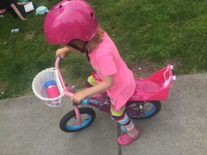 Preschooler on 12 inch wheel bike with baby doll seat attached in rear